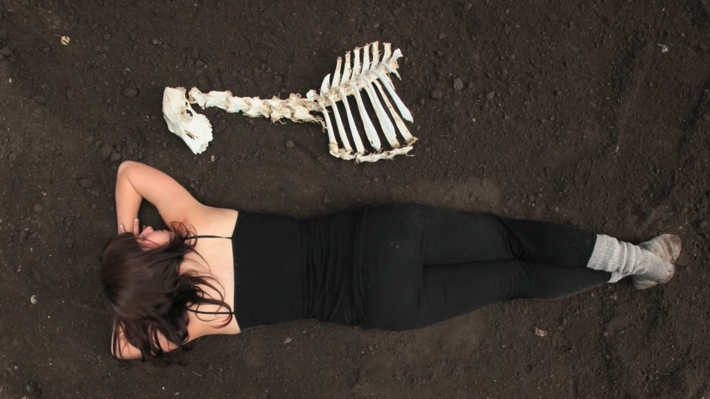 Photo of woman lying next to skeleton of an animal